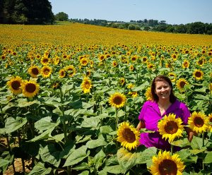 Lisa Collard, a social media manager sitting in a field of sunflowers.