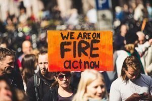 A sign at a climate protest saying We are on fire, act now